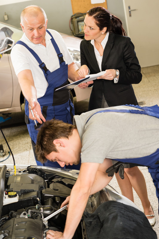 Upset customer showing papers to car mechanic as a friend