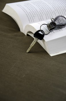 Car keys placed beside a book with a cloth backdrop